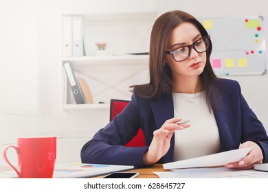 Succesfull woman, female carreer concept. Young businesswoman concentrated at work. Modern office worker in white room interior.
