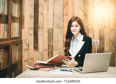 Succesfull woman, female carreer concept. Beautiful young businesswoman sitting by wooden desk with laptop. Modern office worker in room interior.