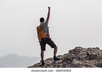 Success and achievement business concept with man celebrating with hand up, arm raised outstretched looking at inspirational landscape view, Greece.