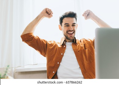 Success and achievement concept. Headshot of businessman, looking at the laptop with happy cheerful smile achieving life goals. Happy Caucasian male student sitting in office make winner gesture.