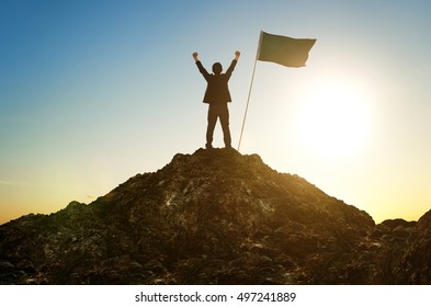 Success and achievement concept , silhouette of businessman with flag on mountain top .