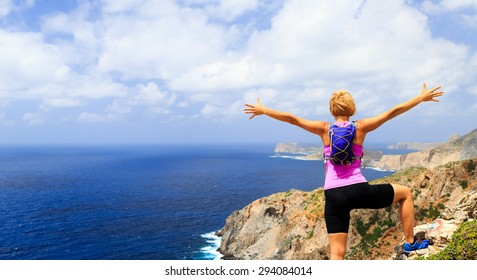 Success achievement running, climbing or hiking accomplishment concept, woman celebrating with arms up raised outstretched hiking, climbing or trail running healthy lifestyle