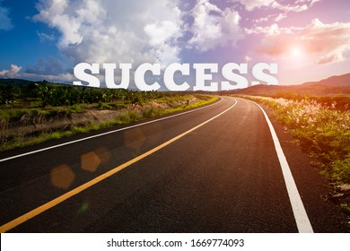 success behind the tree of empty asphalt road at golden sunset and beautiful blue sky. Success concept.
