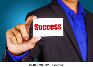 """Success"" black and red text on white card hold by young business man wearing a business jacket - economic, finance and crisis concept"