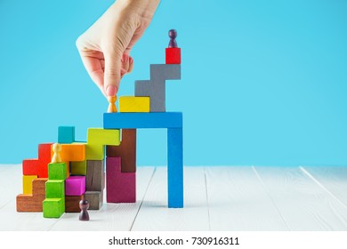 Success building concept. The leader's hand helps in career. Helping hands. Personal development, personal and career growth, progress and potential. People standing on wood block as step stair.