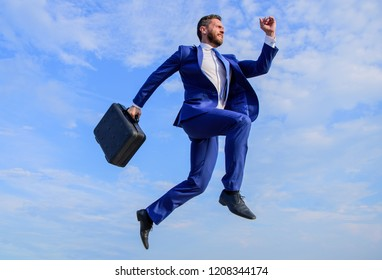 Success in business demands supernatural efforts. Businessman with briefcase jump high in motion forward. Supernatural power. Businessman formal suit make effort to succeed blue sky background.