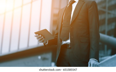 Success business man using tablet phone. Blue Toned Image. Concept businessman lifestyle.