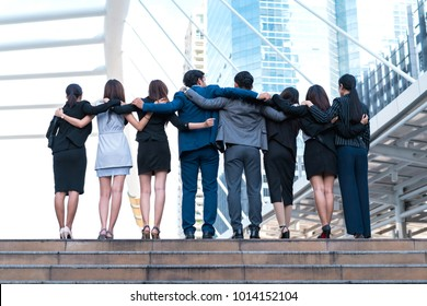 Success business people team arms hug together in the city outdoors, Highly successful startup team, concept of unity, meeting teamwork, performance people and modern lifestyle.