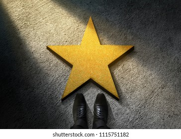 Success in Business or Personal Talent Concept. Top View of Businessman in Shiny Oxford Shoes standing in front of a Golden Star on the Dark Cement Floor