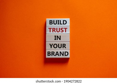 Success business process symbol. Wood blocks stacking as step stair on orange background, copy space. Words 'build trust in your brand'. Business and trust brand concept.