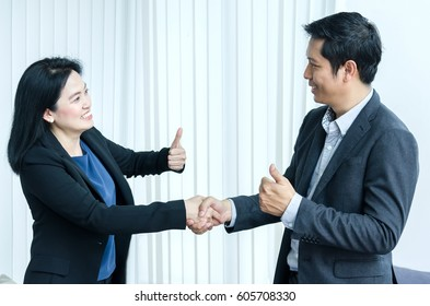 Success business team concept. Asian woman and man handshake and showing thumbs up.