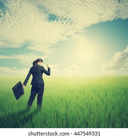 Success Business woman holding bag in green rice field and sun sky.Summer holiday concept.Vintage Tone