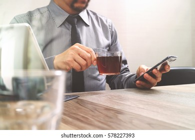success businessman hand using smart phone,digital tablet docking smart keyboard,coffee cup on wooden desk