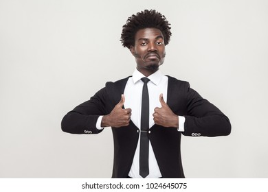Success businessman looking at camera and thumbs up. Studio shot, gray background