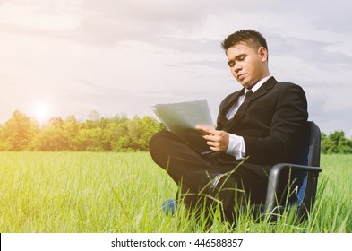 Success businessman, while analyzing data on meadow background,blue sky