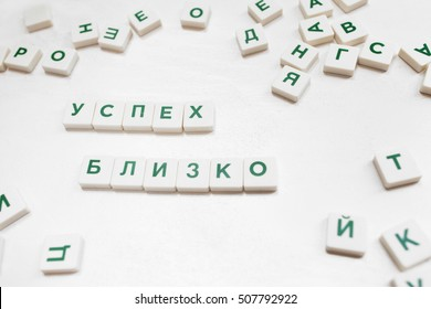 Success Is Close phrase in russian scrabble blocks. Motivational wish constructed from crossword blocks on white background