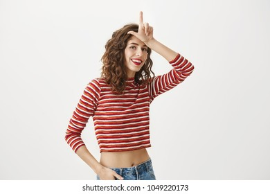 Success comes to determined people. Indoor shot of emotive attractive young woman in red striped cropped top holding index finger near forehead, showing loser gesture while smiling with satisfaction