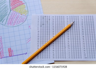 Success concept about education or examination.There are pencil,many charts on graph paper, answers sheet on wooden background.