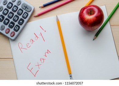 Success concept about education or examination.There are pencils, color, calculator, pages of notebook with Ready Exam word, red apple on wooden background.