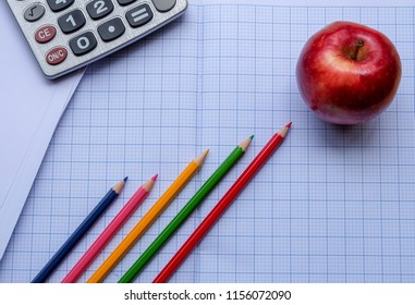 Success concept about education or examination.There are pencils, color, calculator, pages of graph notebook, red apple on wooden background.