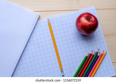 Success concept about education or examination.There are pencils, color, page of graph paper, red apple on wooden background.