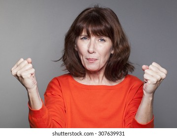 success concept - beautiful mature woman wearing an orange sweater expressing her support and energy with tensed fists tight and up