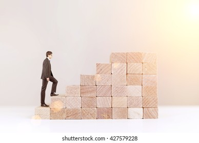 Success concept with businessman climbing wooden block stairs on white background with sunlight