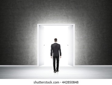 Success concept with businessman standing in concrete interior in front of open double door with bright light
