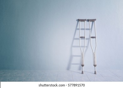Success concept with crutches in the shadow of ladder. Insurance for heath care concept.