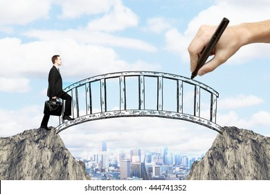 Success concept with hand drawing bridge over gap between two cliffs and businessman walking across it on city background