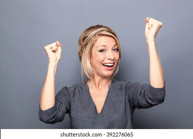 success concept - happy young blond woman winning a competition with fun body language and hands up, gray background studio