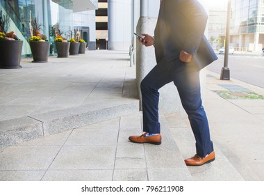 Success concept. Leader Businessman stepping up on business stairs while looking on mobile