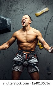 Success concept -shirtless man with perfect fit body flexing his musculs, screaming from effort showing strength and muscles. Strong determined male climber.