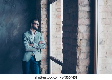 Success concept. Stylish young bearded man is standing near the window and looking far. He looks so classy! in a suit and glasses, with crossed hands