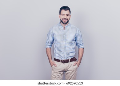 Success concept. Stylish young smiling bearded brunet is standing on pure gray background. He looks so classy! in smart casual outfit, his hands are in pockets