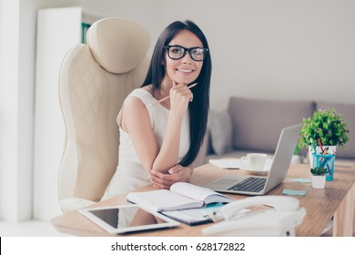 Success conception. Portrait of gorgeous young businesslady in glasses sitting at her workplace in the office