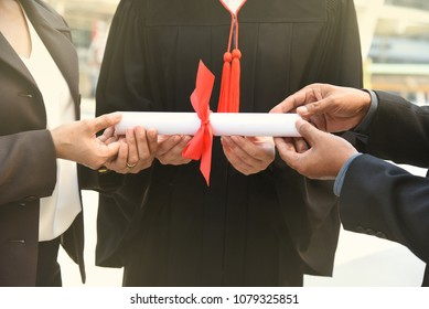 Success degree graduation student and parent father and mother hold hand with diploma certificate ribbon in black gown suit to congrats guarantee finish training school certify finish education