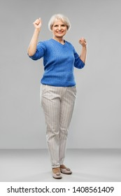 success, emotions and old people concept - portrait of happy senior woman celebrating triumph over grey background