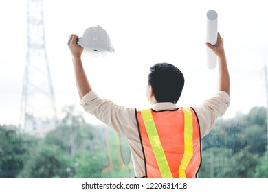Success engineer with document and safty helmet arm up in office back view