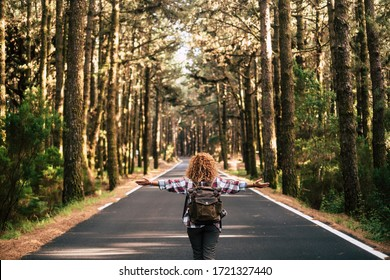 Success and feedom concept with woman and backpack viewed from back and long asphalt road staight in the middle of a high trees nature forest - life after coronavirus lockdown