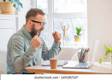 Success and goal achievement concept. Happy businessman feel excitement scream raising fists looking at the laptop achieving life goal, celebrating business success great result make winner gesture - Shutterstock ID 1691087107
