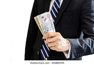 Success and got profit from business with young business man holding Dubai, United Arab Emirates dirham currency,money in a hand isolated on white background,Focus on number 500 on banknote