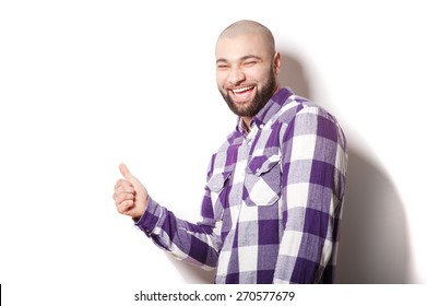 Success! Great job! Happy young bearded man showing his thumb up while standing against white background.