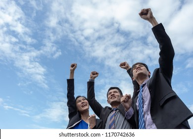 Success group of business people standing and point their hand to the sky with purposely looking away. Fight together for success concept.