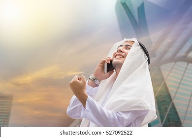 Success and Happiness concept, Portrait of Smiling Arab Middle Eastern Businessman using smartphone, Double exposure photo of city view at sunrise background.