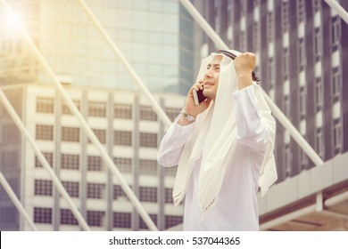 Success and Happiness concept, Portrait of Smiling Arab Middle Eastern Businessman using smartphone in the city background.