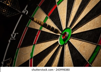 Success hitting target aim goal achievement concept background - dart in bull's eye close up