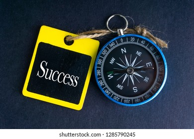 SUCCESS inscription written on tag and compass on black background with selective focus and crop fragment. Business and education concept