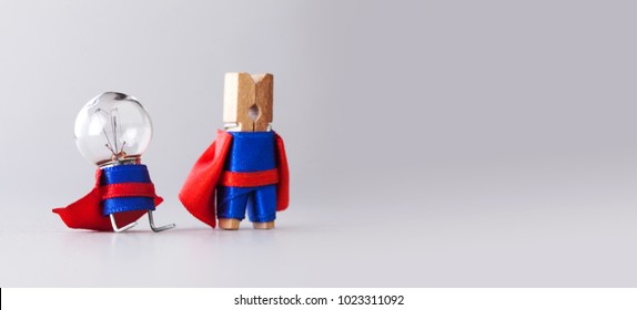 Success management creative concept. Super heroes team clothespin and light bulb, funny toy characters in blue suit and red cape. Gray background copy space. Selective focus.