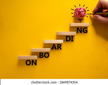 Success onboarding process symbol. Wood blocks stacking as step stair on yellow background, copy space. Businessman hand and light bulb. Word 'onboarding'. Business and onboarding concept.